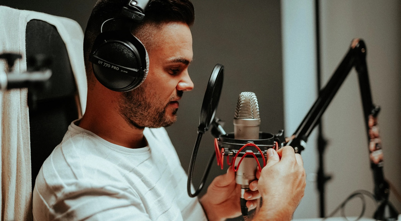 Man wearing headphones, fitting a shock mount to a microphone